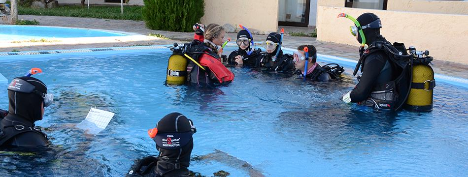 Instructor Development Course students listening to an instructor in a swimming pool