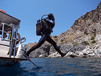 Diver making giant stride from boat on south coast of Crete